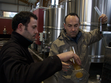 Fezas checks the density of a white wine undergoing fermentation.